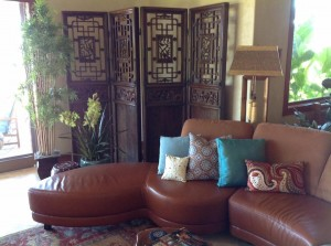 A 17th Century Chinese screen stands proud behind a custom semi-circular leather sofa