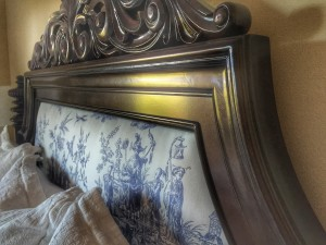 The vintage Chinese toile fabric was upholstered into the headboard and footboard