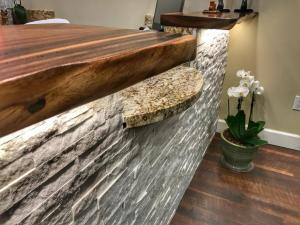 The check-in counter is made from hand-hewn Monkey Pod, with a natural stone facing and a granite counter top.