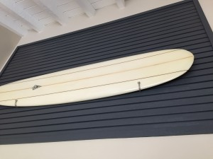 The old balcony has been reconfigured with slats for airflow - all acting as a frame for the vintage surfboard